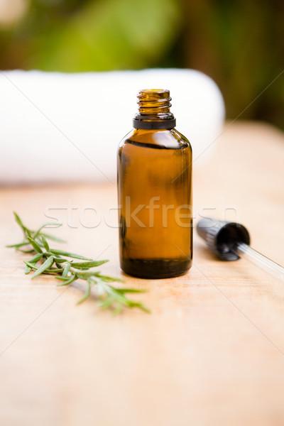 Aromatherapy oil bottle by rosemary on table Stock photo © wavebreak_media