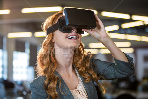 Smiling businesswoman using virtual reality simulator Stock photo © wavebreak_media