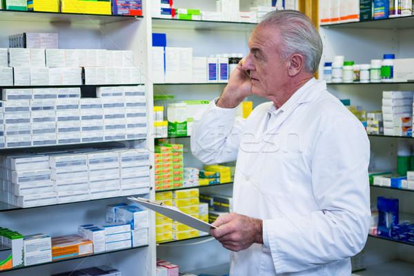 Pharmacist talking on mobile phone while checking medicines Stock photo © wavebreak_media