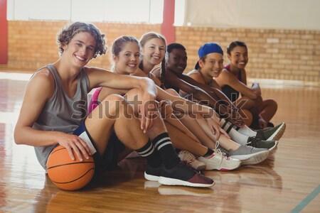 Portrait of high school kids sitting on the floor in basketball court indoors Stock photo © wavebreak_media