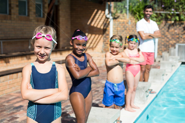 Confident little swimmers with male instructor at poolside Stock photo © wavebreak_media