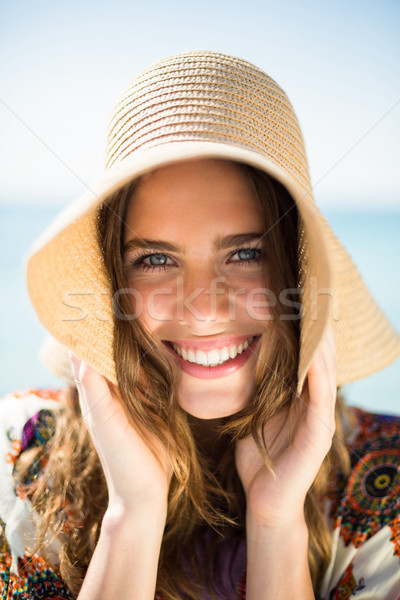 Portrait of happy young woman wearing hat at beach Stock photo © wavebreak_media