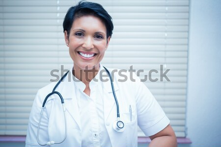 female doctor wearing breast cancer awareness pink ribbon with crossed arms on a white background Stock photo © wavebreak_media