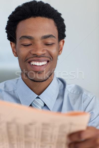 Smiling Afro-American businessman reading a newspaper Stock photo © wavebreak_media