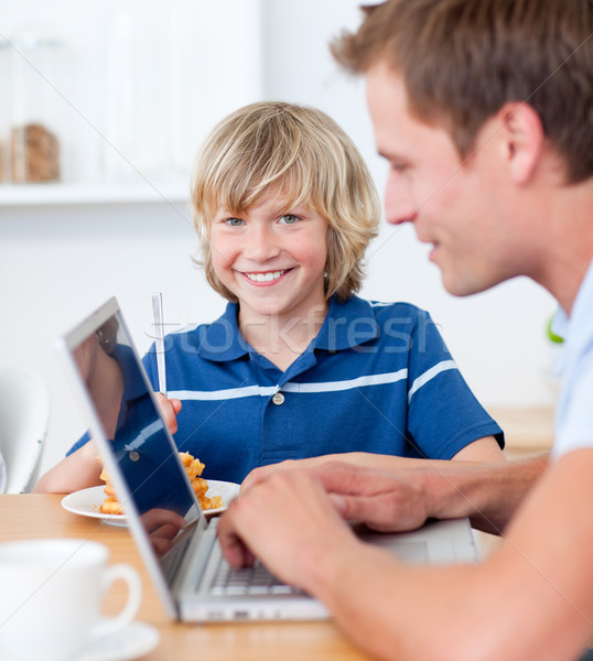 Adorable boy having breakfast while his father using a laptop Stock photo © wavebreak_media