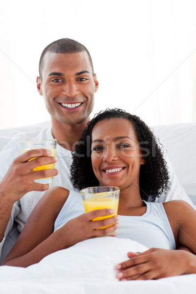 Enamored couple drinking lying on their bed Stock photo © wavebreak_media