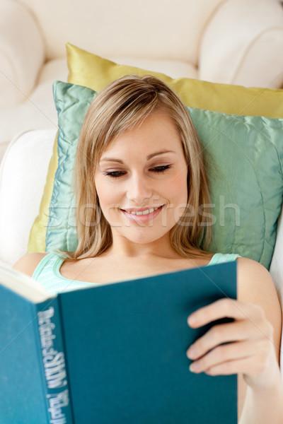 Smiling woman reading a book lying on a sofa Stock photo © wavebreak_media
