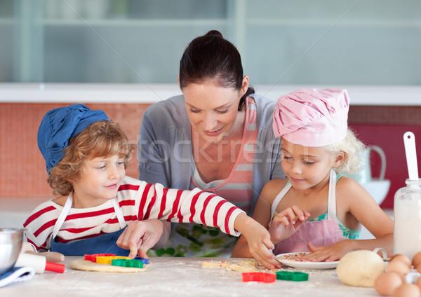 Beautiful mother helping their chilldren baking cookies in the kitchen Stock photo © wavebreak_media