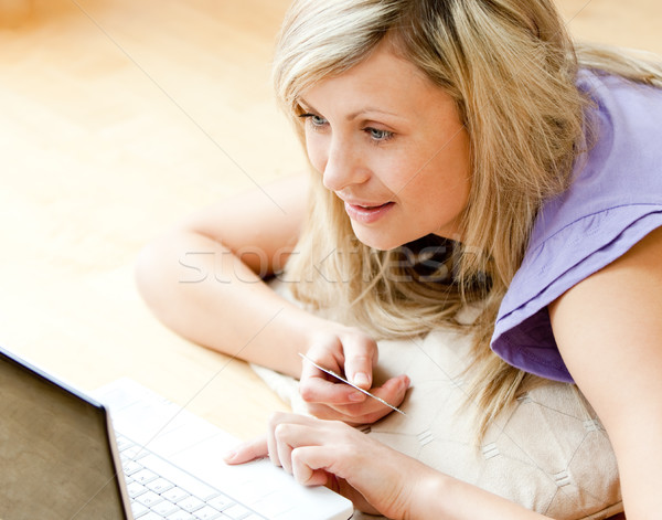 Bright woman shopping on-line lying on a sofa at home Stock photo © wavebreak_media