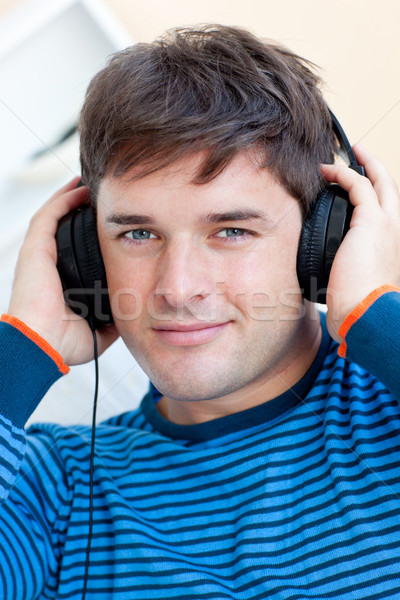peaceful man listening music using headphones smiling at the camera in the living-room Stock photo © wavebreak_media