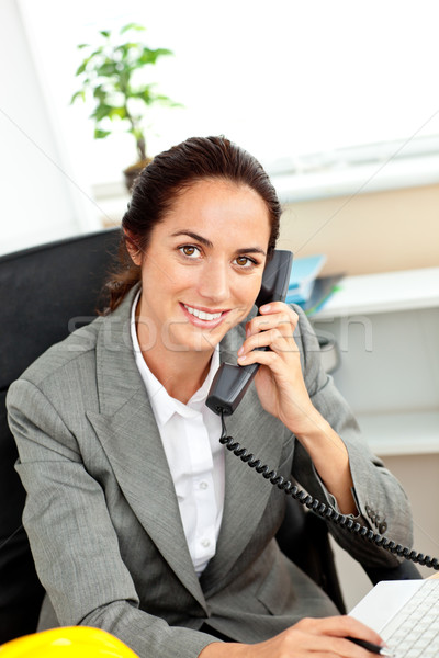 Busy hispanic female architect using her laptop while talking on phone in her office Stock photo © wavebreak_media
