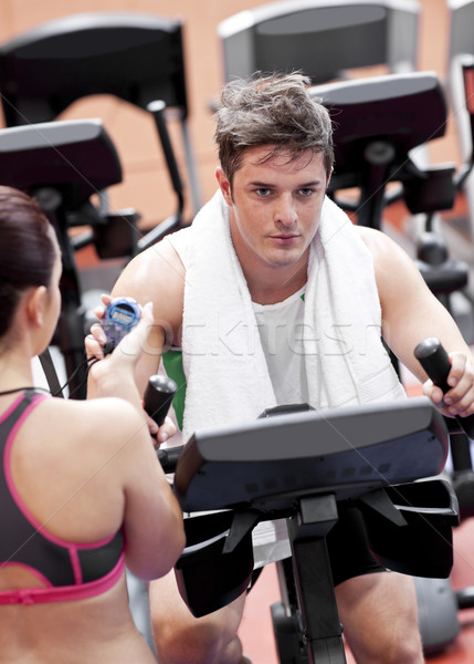 Female coach using a chronometer while man is doing physical exercises in a fitness centre Stock photo © wavebreak_media