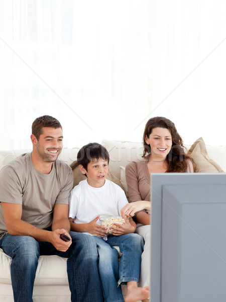 Happy family watching television while eating popcorn together Stock photo © wavebreak_media