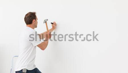 Rear view of a man hammering against a white wall standing on a ladder Stock photo © wavebreak_media