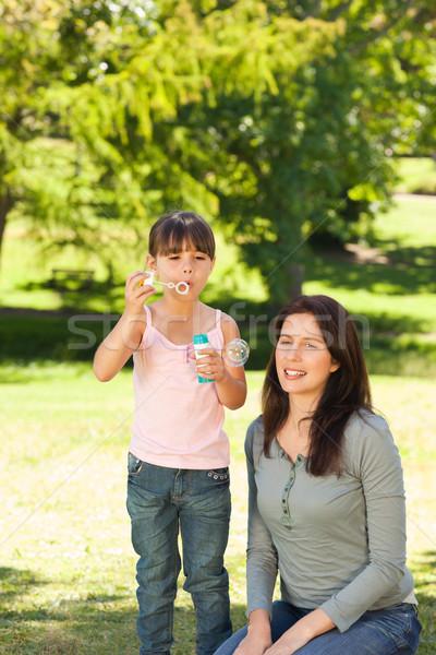 Lány buborékfújás anya park kéz arc Stock fotó © wavebreak_media