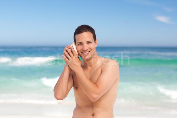 Uomo ascolto shell felice mare sfondo Foto d'archivio © wavebreak_media
