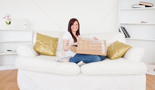 Beautiful red-haired female opening a carboard box while sitting on a sofa in the living room Stock photo © wavebreak_media