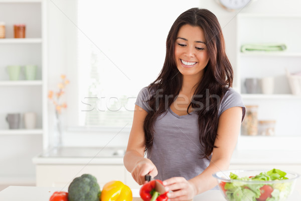 Stock photo: Beautiful woman cooking vegetables while standing in the kitchen