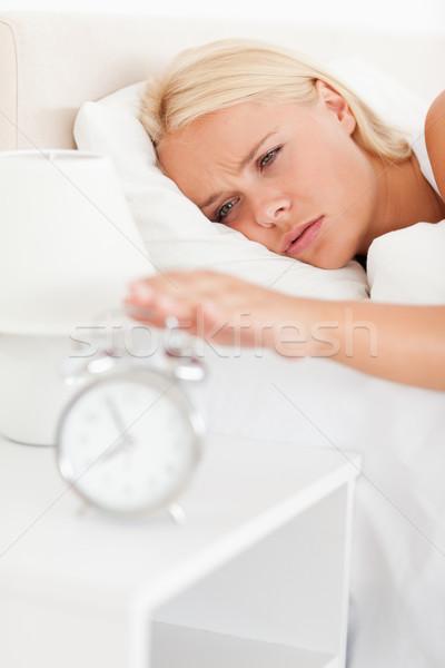 Portrait of a woman awaken by an alarmclock  in her bedroom Stock photo © wavebreak_media