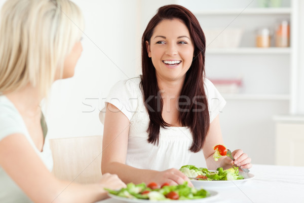 Portrait of laughing Women eating salad in a kitchen Stock photo © wavebreak_media