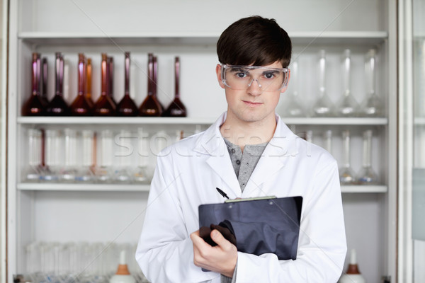 Male science student writing on a clipboard in a laboratory Stock photo © wavebreak_media