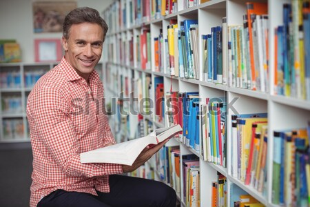 Smiling male student holding a book in a library Stock photo © wavebreak_media