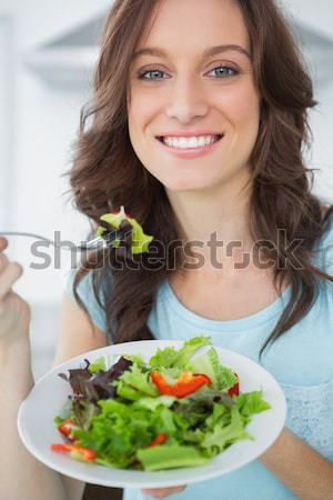 Happy smiling woman offering some salad against a white background Stock photo © wavebreak_media