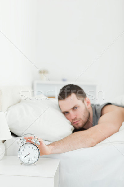 Portrait of a man being awakened by an alarm clock in his bedroom Stock photo © wavebreak_media