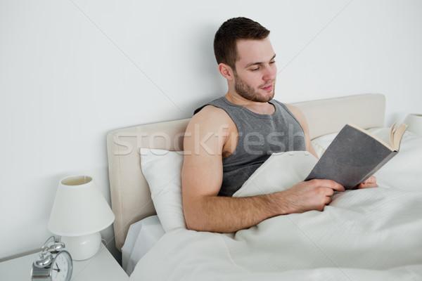 Young man reading a novel in his bedroom Stock photo © wavebreak_media