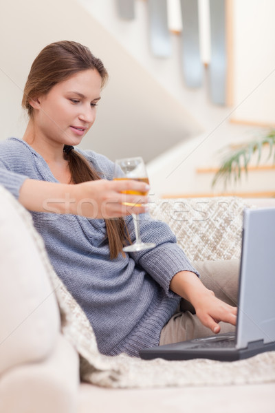 Stock photo: Portrait of a woman having a glass of wine while using her notebook in her living room
