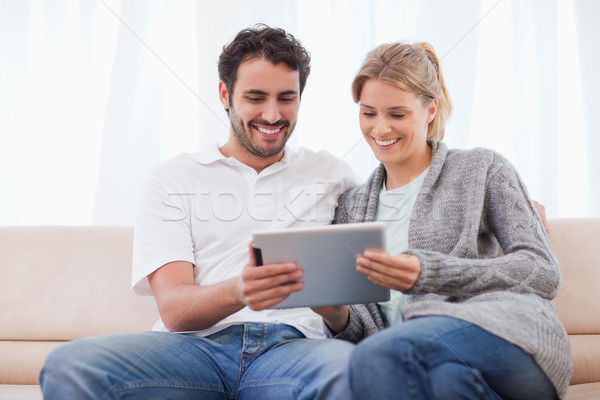 Couple using a tablet computer in their living room Stock photo © wavebreak_media