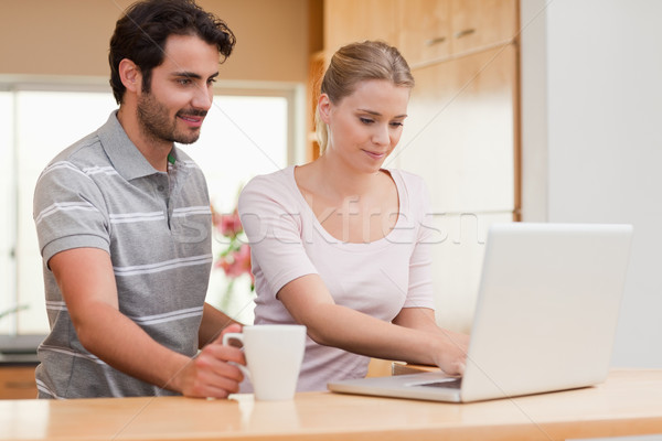 Couple using a laptop while having coffee in their kitchen Stock photo © wavebreak_media