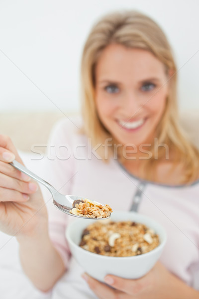 A focused shot of a woman offering a spoon of cereal, the shot focused on the spoon itself. Stock photo © wavebreak_media