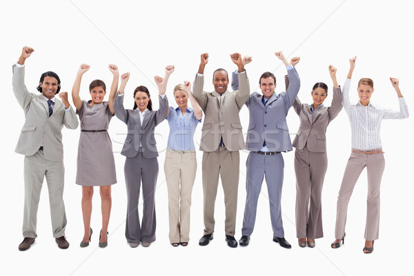 Happy business team raising their arms against white background Stock photo © wavebreak_media