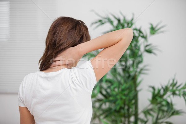 Brunette massaging her painful neck in a room Stock photo © wavebreak_media
