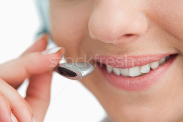 Stock photo: Close-up on a smiling businesswoman mouth speaking in headset against white background