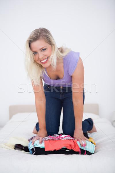 Mosolyog fiatal nő zárt bőrönd ágy női Stock fotó © wavebreak_media