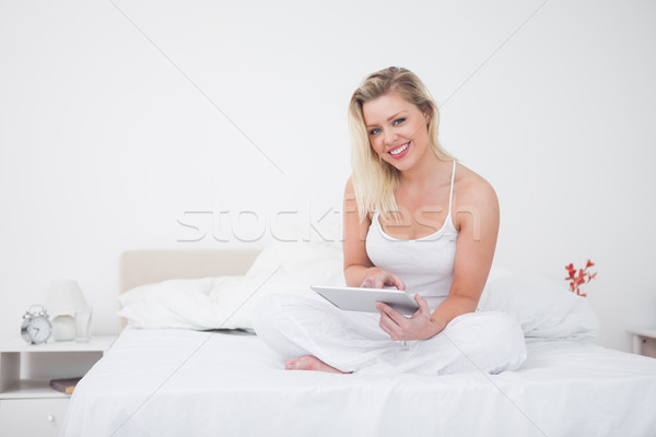 Blonde using an ebook reader while sitting on a bed Stock photo © wavebreak_media