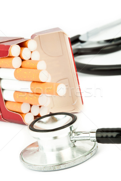 Cigarette pack next to a stethoscope against a white background Stock photo © wavebreak_media