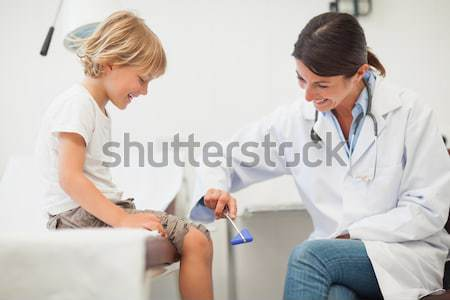 Doctor smiling to a child in examination room Stock photo © wavebreak_media