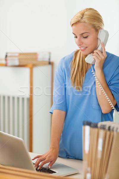 Infirmière appelant utilisant un ordinateur portable hôpital réception Photo stock © wavebreak_media