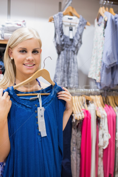 Happy woman holding up blue shirt in clothes store Stock photo © wavebreak_media