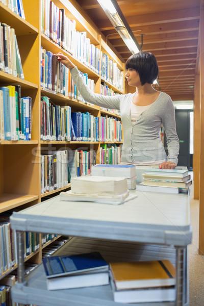 Bibliotecário em pé olhando mulher trabalhando Foto stock © wavebreak_media
