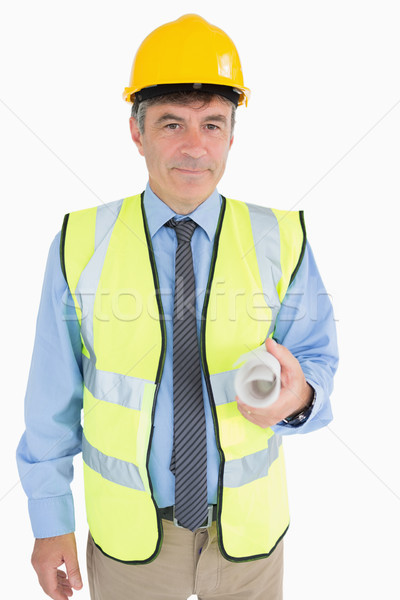 Man in helmet and vest holding a rolled up plan while smiling Stock photo © wavebreak_media