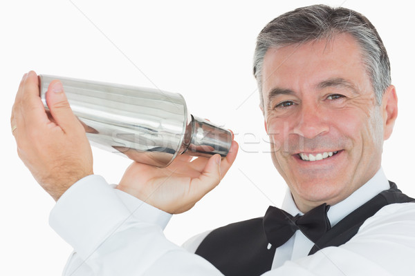 Happy waiter in suit shaking drink in cocktail shaker on white background Stock photo © wavebreak_media