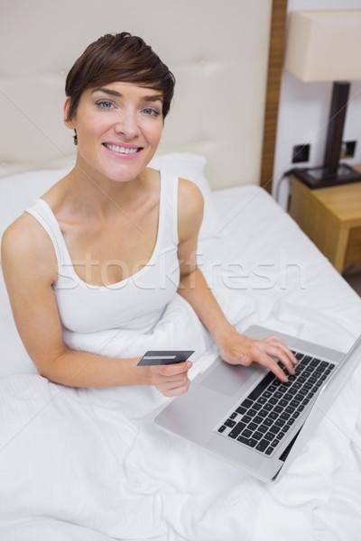 Glimlachende vrouw winkelen online bed hotelkamer Stockfoto © wavebreak_media