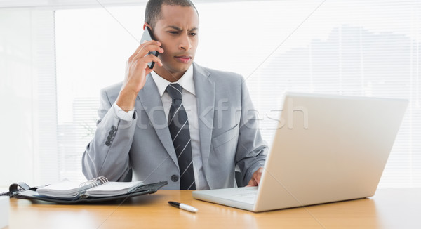 Concentrated businessman using laptop and cellphone Stock photo © wavebreak_media