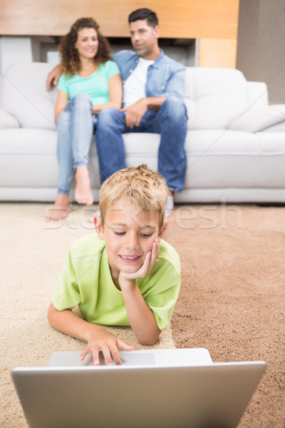 Cute little boy using laptop on the rug with parents sitting sof Stock photo © wavebreak_media