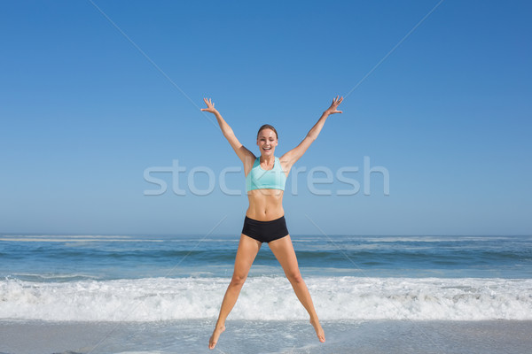 Fit woman jumping on the beach with arms out Stock photo © wavebreak_media