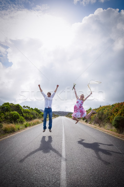 Excited couple jumping on the road Stock photo © wavebreak_media